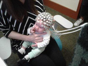 Image of a one-month-old infant with an EEG cap.